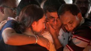 Ramesh Vaya, centre, is comforted by family members after lighting the funeral pyre for his wife Malti, who was shot dead in the attack on the Westgate Mall, at her funeral at the Hindu Crematorium in Nairobi, Kenya Tuesday, 24 September 2013.
