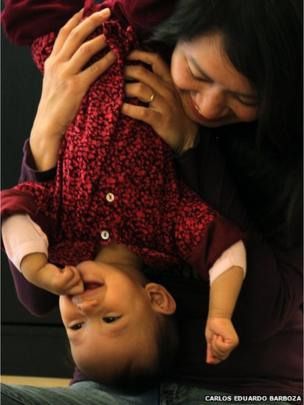 Girl being held upside down by mum