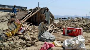 Survivors collect their belongings in the quake-hit town of Awaran, Balochistan, on 25 September 2013