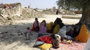 Quake survivors sit beside the debris of their destroyed homes in Awaran on 25 September 2013