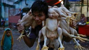 A man stops for a photograph while carrying chickens at a wholesale market in Yangon