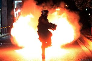 A molotov cocktail explodes in front of a riot policeman in Athens.