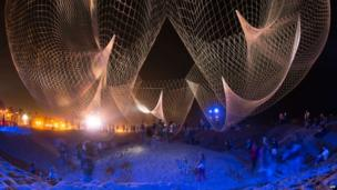 """Visitors explore the creation of artist Janet Echelman """"The Space Between Us"""" during Glow 2013 on September 29, 2013 at the beach in Santa Monica, California. Glow is an all-night cultural experience featuring original commissions by artists that re-imagine Santa Monica Beach as a playground for thoughtful and participatory temporary artworks."""