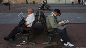 Pensioners read a free newspaper as they sit on public benches in Madrid