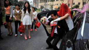 A groom carries his bride out of a car as part of a tradition on their wedding day in Wuhu, China