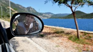 Woman taking picture in wing mirror