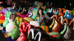 A lady in the middle of the colourful Gromit models