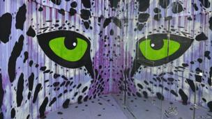 striking pair of green eyes in tower block art project Tour 13 in Paris