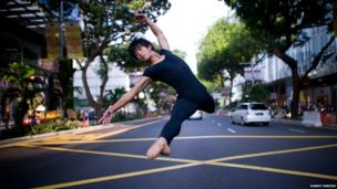 A ballet dancer leaping along one of Singapore's main roads