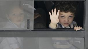 A boy waves from the window of a bus as he waits to board a ship in Lampedusa, Italy, (4 Oct. 2013)