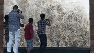 People take pictures of a storm surge under the influence of Typhoon Fitow in Wenling, Zhejiang province, 6 October 2013