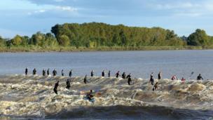"""People surf the """"Mascaret"""", a tidal wave on the Dordogne river, at Saint-Pardon-de-Vayres, south-western France (6 October 2013)"""