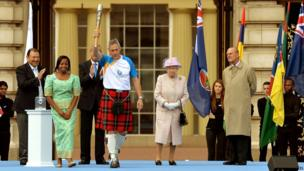 Allan Wells holds the baton aloft