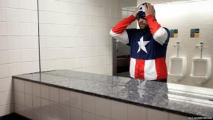 A man dressed as Captain America adjusts his mask after washing his hands in the bathroom at the Comic Con pop culture event in New York