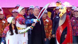 "Russian President Vladimir Putin (centre) with Russian ice-skaters Lina Fyodorova (left) and Maksim Miroshkin ""second left)"
