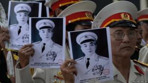 Veterans hold portraits of late General Vo Nguyen Giap as they line up along a street to pay their final respects in Hanoi