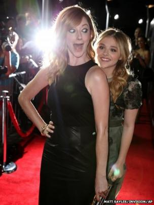 Chloe Grace Moretz (right) surprises Judy Greer on the red carpet of the world premiere of Carrie at the ArcLight Hollywood in Los Angeles