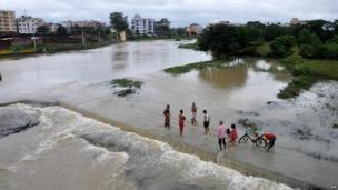 Indian residents stand in the waters of the overflowing Subarnarekha River