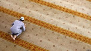 Man praying on colourful rug in a mosque in Singapore.