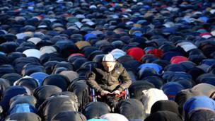 Man in wheelchair among hundreds of men kneeling in prayer at a mosque in Moscow.