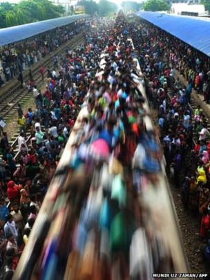 Bangladeshi commuters ride on a train in Dhaka