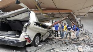 Residents inspect a car after a concrete block fell on it during an earthquake in Cebu city