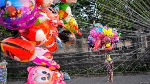 Woman holding colourful balloons outside a monument in Denpasar, Bali