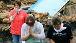 Landslide survivors offer prayers as the body of a victim is carried by rescue workers in the rubble of houses in Oshima damaged by landslides after a powerful typhoon hit Izu Oshima island, about 120km (75 miles) south of Tokyo, 16 October 2013