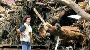A woman reacts in front of collapsed houses following a landslide caused by Typhoon Wipha on Izu Oshima island, south of Tokyo, in this photo taken by Kyodo 16 October 2013