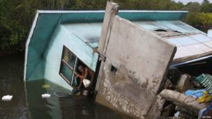 A resident looks out from the window of his house that fell into a river after an earthquake, in central Philippines