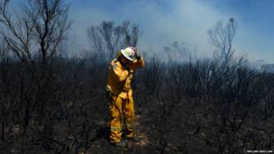 A volunteer firefighter holds onto his helmet in the strong winds as he surveys the damage in the Mount York fire in the Blue Mountains, west of Sydney, Australia