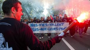 """Employees of the Joue-les-Tours based French tyre manufacturer Michelin plant hold a banner that reads """"Our lives are worth more than their profits"""" as they protest on 24 October 2013 in Tours, central France, against the closing of the plant"""