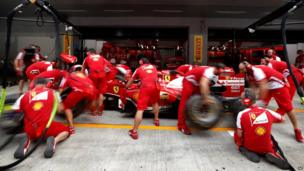Ferrari team mechanics practice a tyre change in the pits ahead of the Indian Formula One Grand Prix at the Buddh International Circuit in Noida, India, on 24 October 2013