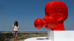 A tourist poses beside a two-metre-high blood red sculpture of a head blowing bubble gum by Qian Sihua, which is part of the Sculpture by the Sea exhibition which runs on the Bondi to Tamarama coastal walk in Sydney.