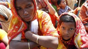 A garment worker who survived the Rana Plaza building collapse, takes part in a protest with her child to demand for compensation, on the six month anniversary of the incident, in front of the site in Savar.