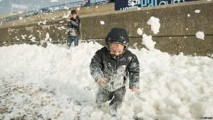 Will Brewer, 4, plays in the foam washed ashore on the Brighton seafront as high winds pick up ahead of an expected storm