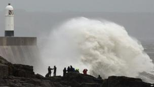 People stand on the rocks as large waves break against barriers at the harbour in Porthcawl, South Wales on 27 October, 2013 as a predicted storm starts to build.