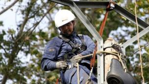 A worker repairs power lines damaged during the storm in in Fourches, north-western France (28 October 2013)