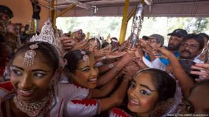 Traditional Sri Lankan dancers reach for the baton during arrival celebrations.