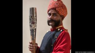 The Queen's Baton is held by an Indian hotel concierge in Agra, India.
