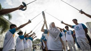 Athletes with fencing foils present a guard of honour for the Queen's Baton in Brunei.