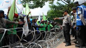 Indonesian police officers block the protesters with barbed wire barricades during a protest demanding higher wages in Surabaya, Indonesia