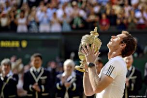 Britain's Andy Murray holds the winner's trophy after beating Serbia's Novak Djokovic in the men's singles final at the 2013 Wimbledon Championships