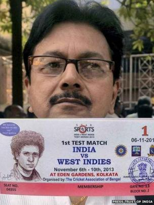 A man showing a ticket, bearing the picture of Sachin Tendulkar for India's Test match against West Indies in Calcutta