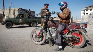 A police trooper checks the documents of a biker in Sanaa