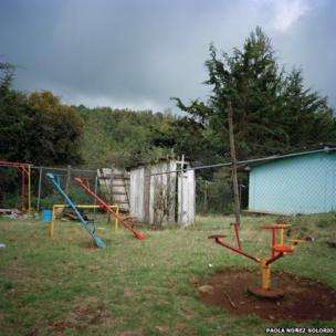 Kindergarten playground with wooden bathroom in background in Las Palmitas, Morelia, Michoacan.