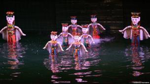 Wooden puppets in waist deep water