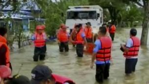 Rescuers wade through flood waters caused by Typhoon Haiyan in Mindoro, Philippines