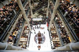 Brokers and underwriters line the balconies and escalators of the Lloyd's of London building during a service