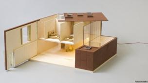 Dolls house made of wood and Perspex with gold bedding and chair